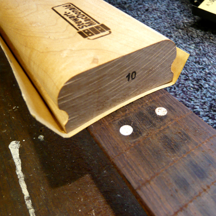 Removing grooves from a fingerboard: